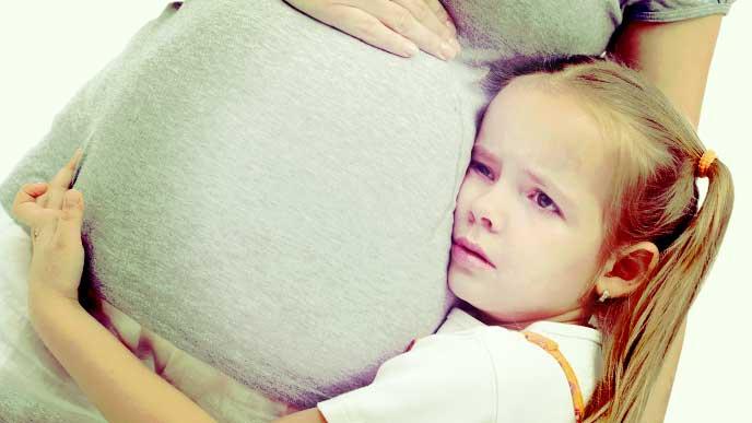 妊娠しているママのお腹に泣きながら抱きついている女の子
