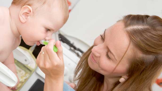 赤ちゃんに離乳食を食べさせているママ