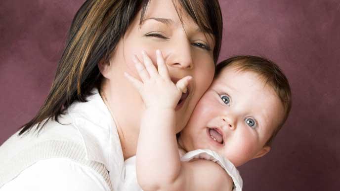 赤ちゃんに頬ずりしている母親