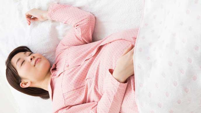 ピンクの薄手のマタニティパジャマで寝てる妊婦さん