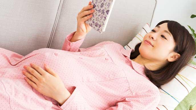 ピンクの部屋着ワンピースでソファーに横になりながら本を呼んでる妊婦さん