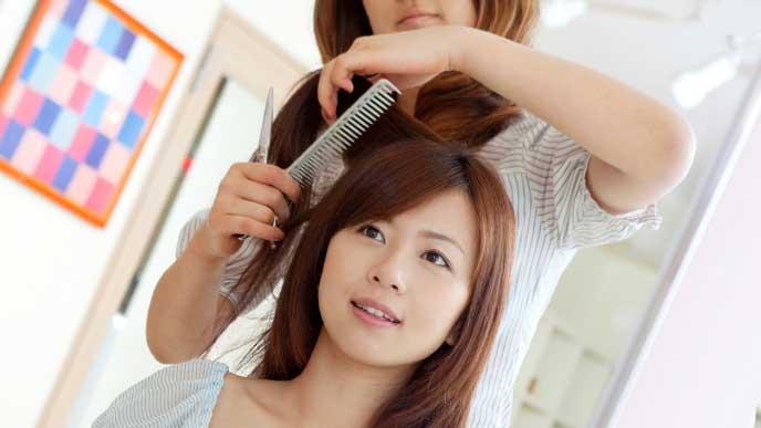 美容室で髪の毛をカットしてもらっている女性