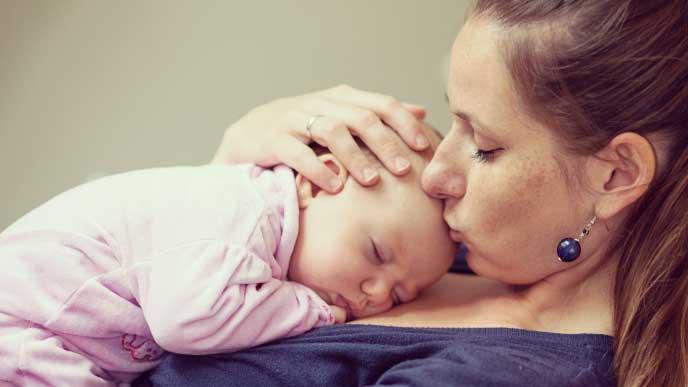 ロングヘアーをアップにまとめて赤ちゃんを抱っこしているママ