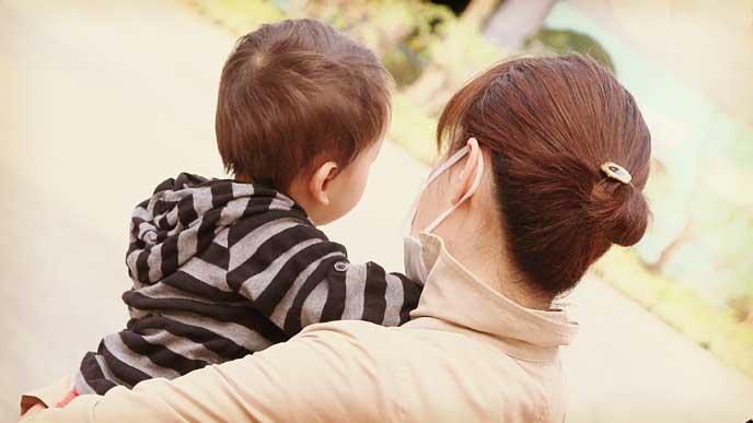 髪をまとめて赤ちゃんを抱っこしているママの後ろ姿