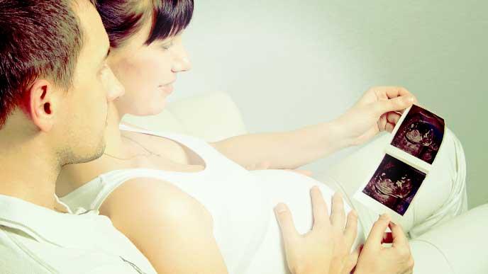 旦那さんと一緒にエコー写真を見てる妊婦さん
