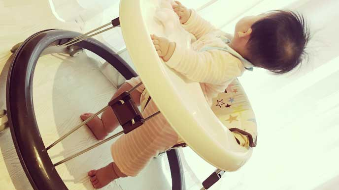 歩行器に乗って窓から外を見ている赤ちゃんの後ろ姿
