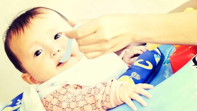 歩行器に乗りながら離乳食を食べている赤ちゃん