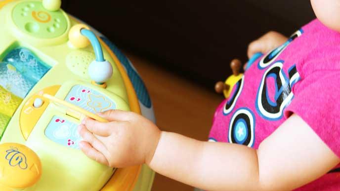 歩行器についてる玩具で遊んでいる赤ちゃん