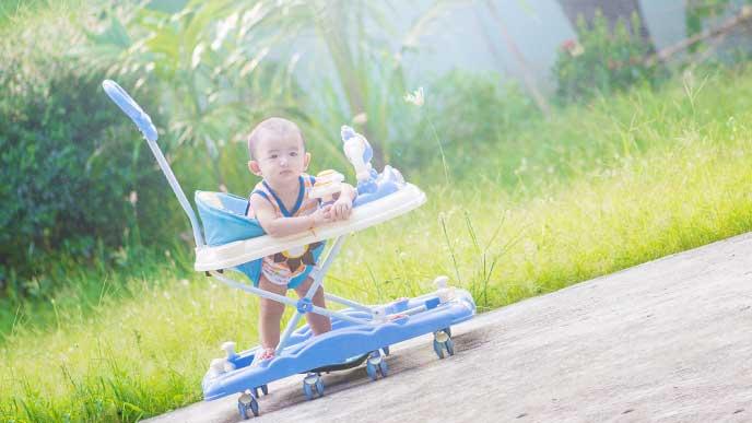 外の道路を歩行器に乗って歩いている赤ちゃん