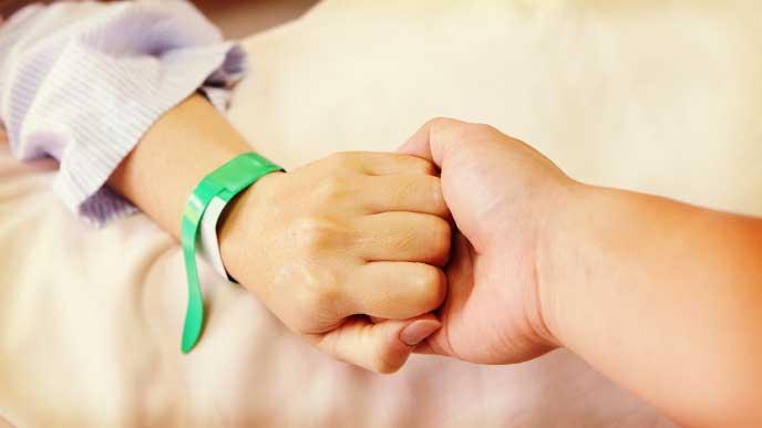 帝王切開の手術中に奥さんの手を握る旦那さんの手