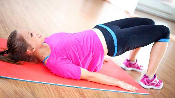 仰向けに寝た姿勢から腰を持ち上げる体操をする女性