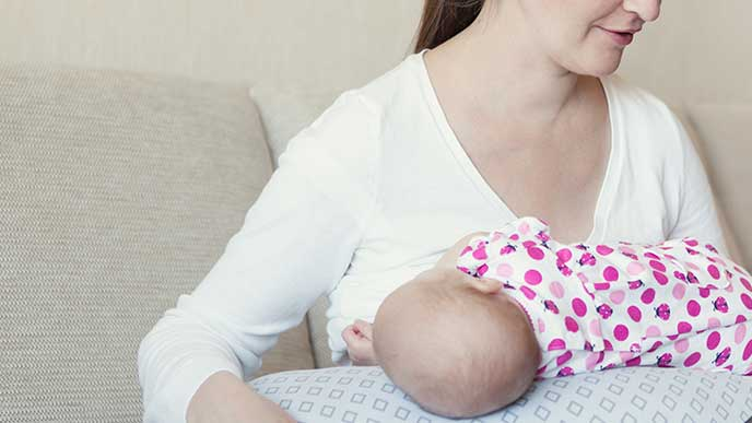 授乳クッションに赤ちゃんをのせて授乳する母親