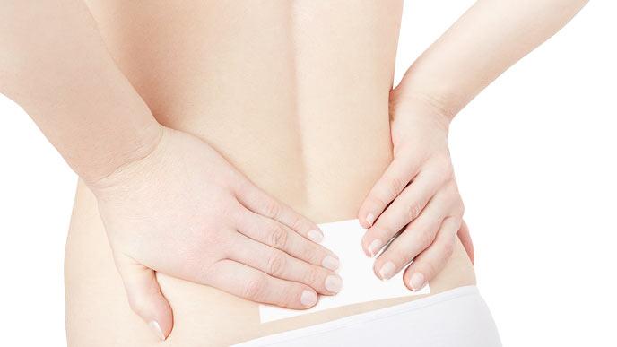 腰に湿布を貼る女性