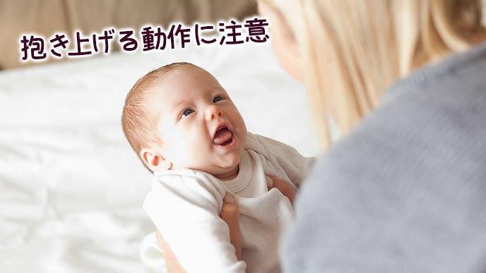 ベッドから赤ちゃんを抱きあげる母親