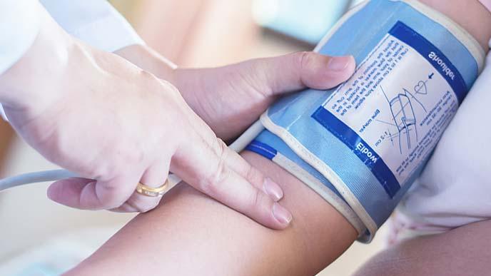 病院で血圧を測ってもらってる妊婦さん