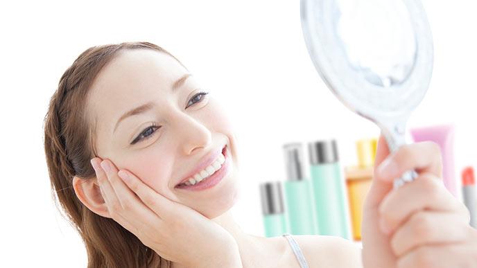 手鏡で肌の手入れをする女性
