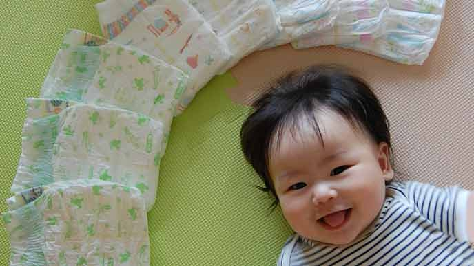 オムツの傍で笑顔の赤ちゃん