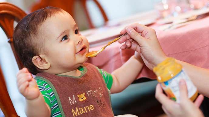 よだれかけをして離乳食を食べる赤ちゃん