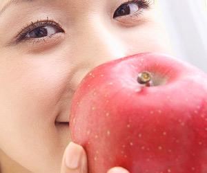 リンゴを顔の前に持つ女性