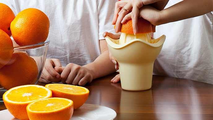 オレンジを半分にカットして搾る