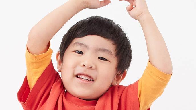 万歳ポーズの幼児の笑顔