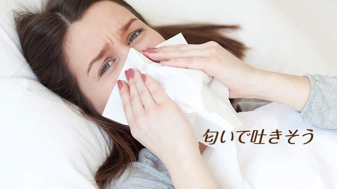 病院のベッドで鼻をティッシュで押さえる妊婦