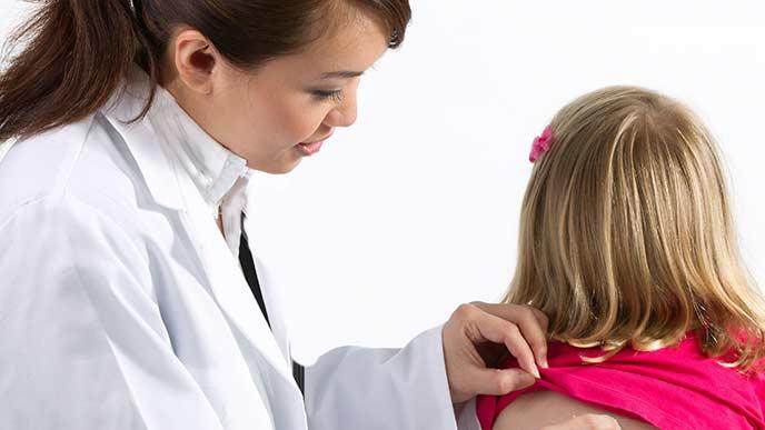 子供の背中を診察する女性医師