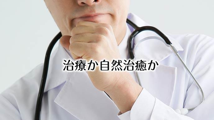 腕組みして考える医師