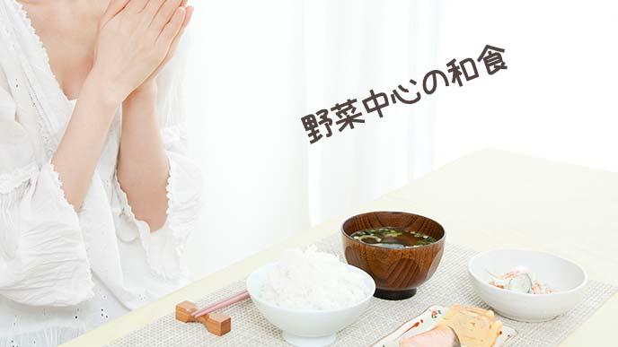 野菜中心の和食の前で手を合わせる女性