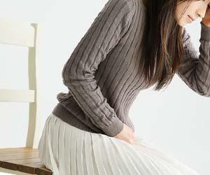 椅子の上で腰を浮かせる女性