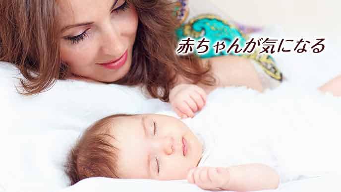 隣で眠る赤ちゃんの顔を覗き込む母親