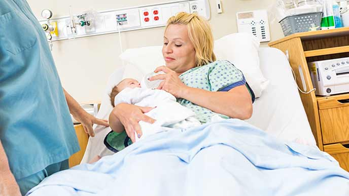 個室で赤ちゃんに授乳させる母親