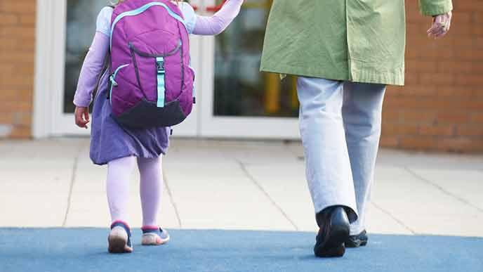 2歳児の手を引いて歩く母親