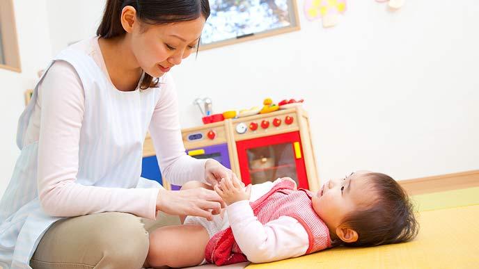 赤ちゃんのオムツを替えようとしている保育士さん
