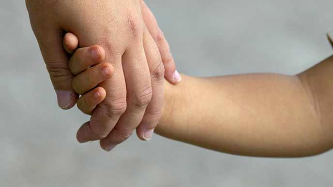子供の手を引く母の手