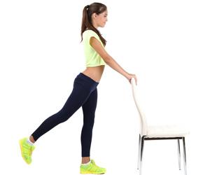 椅子を掴んだ姿勢で立ち、体操する女性