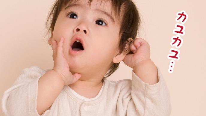 耳に違和感を感じて耳を触っている赤ちゃん