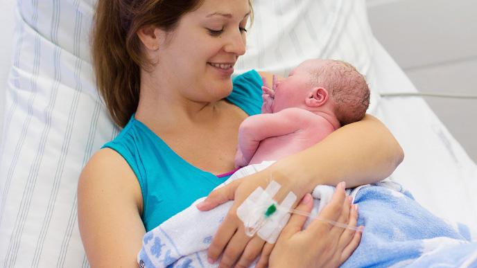 生まれたばかりの赤ちゃんを抱くママ