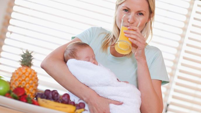 子供を抱きジュースを飲む女性