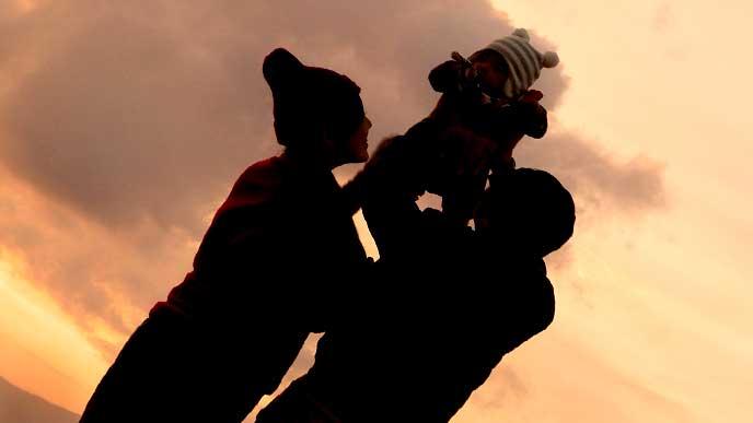 夕焼けをバックに赤ちゃんを二人で抱き上げてる夫婦