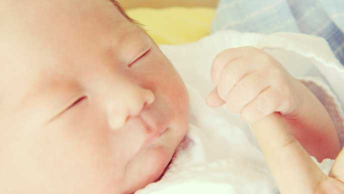 母親の指を握っている赤ちゃん