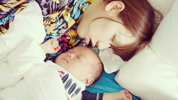 赤ちゃんと一緒に布団で寝てるママ