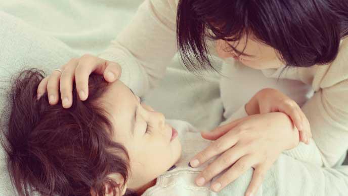 寝てる子供の眉毛を見てるママ