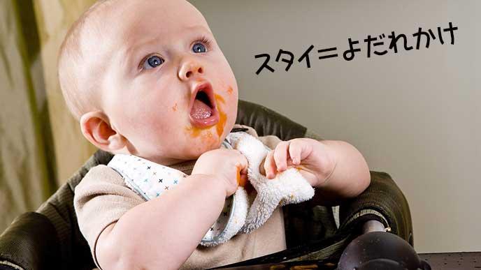 ベビーフードで口の周りが汚れた赤ちゃんがスタイを掴む