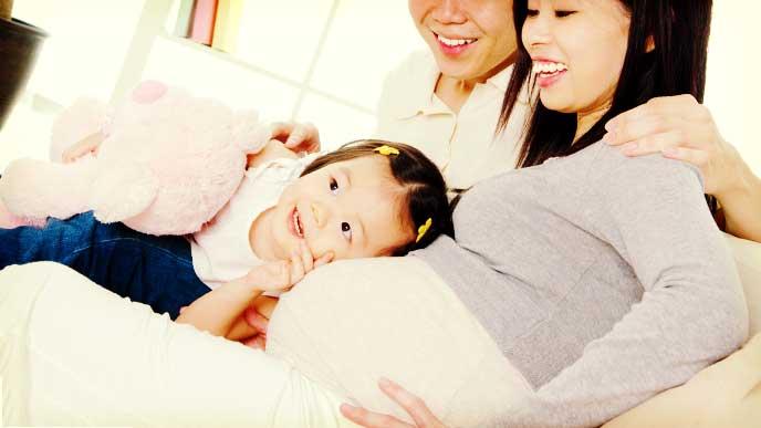 妊娠してる母親のお腹に耳をあてて音を聞いてる女の子