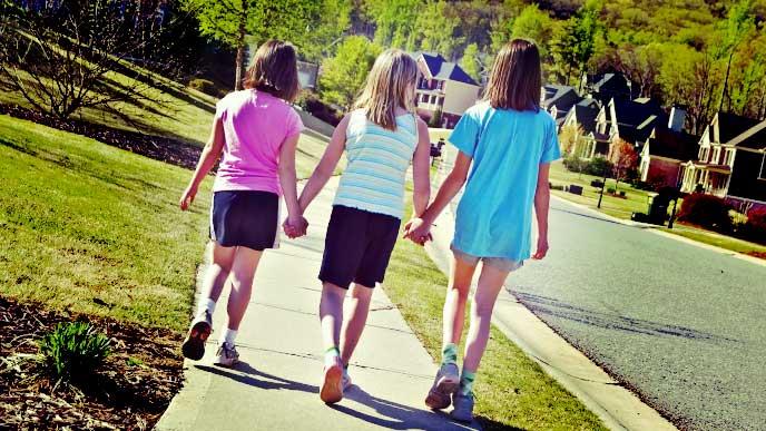 手を繋いで並んで歩いている3姉弟