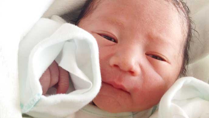 ちょっと目が開いてる生まれたばかりの新生児
