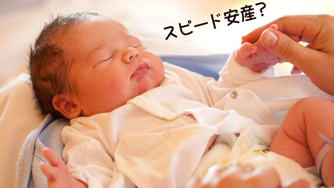 新生児の指を掴む母親