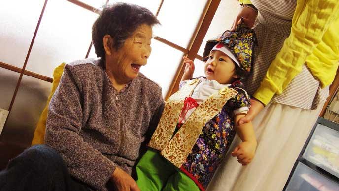 兜と着物を着た赤ちゃんを見て笑顔の祖母