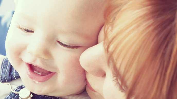 赤ちゃんの柔らかいホッペにキスをする母親